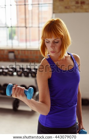 Serious slender toned young woman working out in a gym doing weightlifting with a dumbbell in her flexed hand, close up view - stock photo