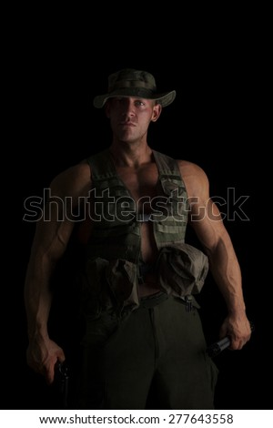 Serious soldier with gun and flashlight isolated on black background. War on terror. - stock photo