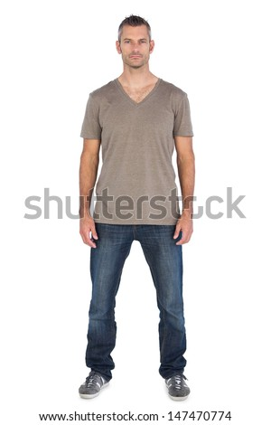 Serious standing man looking at the camera on a white background - stock photo