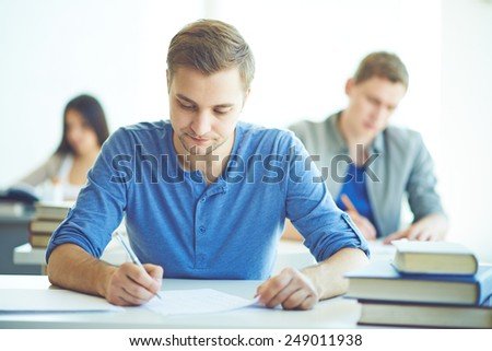 Serious student during written exam - stock photo