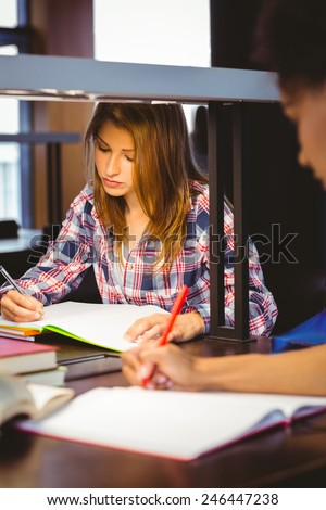 Serious student sitting at desk writing in notepad in library - stock photo