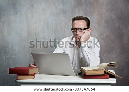Serious student study with laptop and old books - stock photo
