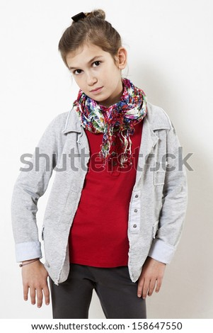 serious student wearing grey suit and color scarf standing near white wall - stock photo