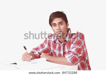Serious student writing notes - stock photo