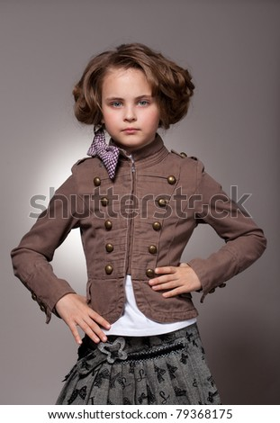 Serious stylish little girl with bow looking at camera - stock photo