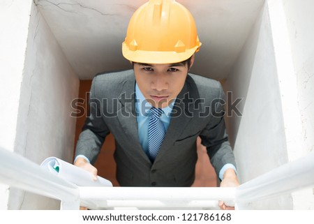 Serious supervisor climbing the ladder holding rolled blueprints - stock photo