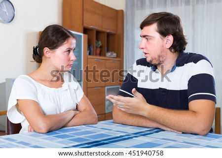 Serious talking about relationships between young couple at home