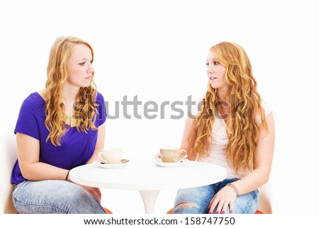 serious talking women sitting at a coffee table on white background - stock photo