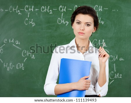 Serious teacher with folder stands at the blackboard