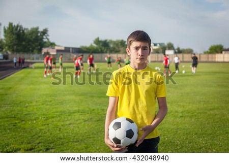 serious teenage boy with a soccer ball in his hand against the background of the stadium. Sports training in the field. - stock photo