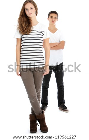 Serious teenage girl in trendy modern clothing posing full body with her brother with the girl in the foreground isolated on white