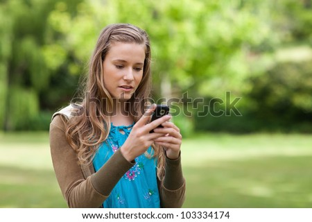 Serious teenager sending a text with her cellphone while standing in a park - stock photo