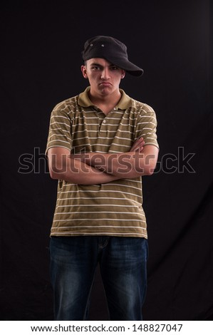 serious teenager try to be cool standing with the cap put on one side and arms crossed