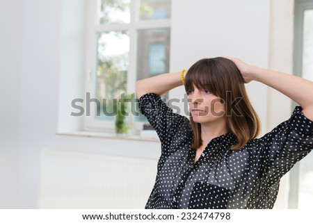 Serious thoughtful businesswoman sitting in the office with her hands clasped behind her head staring into space in deep contemplation - stock photo