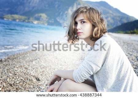 serious thoughtful girl in  sitting on the beach - stock photo