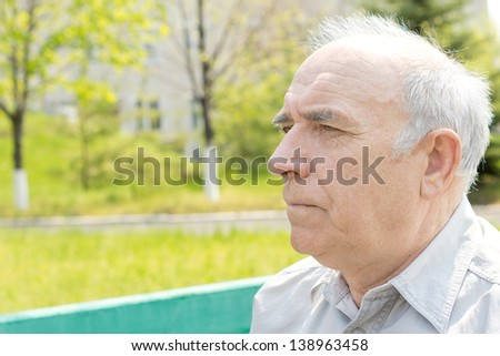 Serious thoughtful senior man sitting sideways to the camera staring into the distance, head and shoulders portrait in a rural park - stock photo