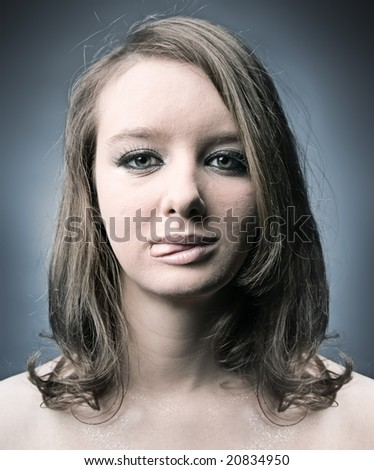 Serious thoughtful woman showing tongue. Soft blue tint. - stock photo