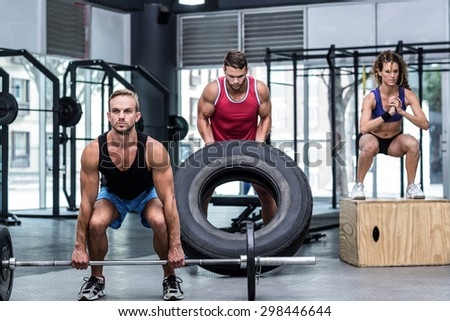 Serious three muscular people lifting and jumping in crossfit gym - stock photo