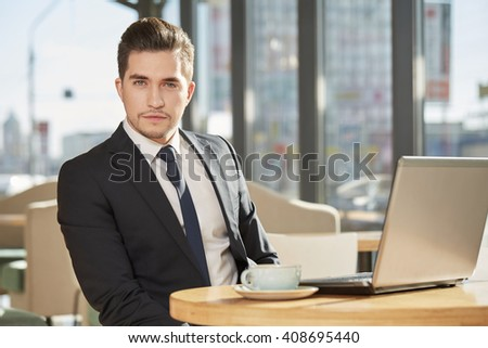 Serious to the bone. Portrait of a handsome young businessman wearing a suit looking to the camera seriously sitting at the local coffee shop