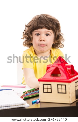 Serious toddler boy sitting at table at kindergarten - stock photo