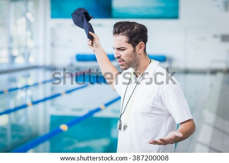 Serious trainer angry at someone at the pool - stock photo