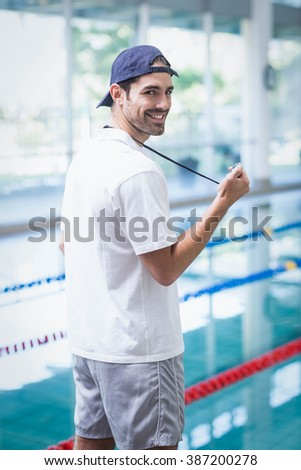 Serious trainer looking at stopwatch at the pool - stock photo