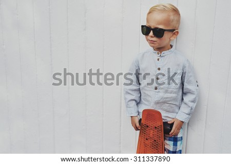 Serious trendy little boy posing with his skateboard wearing a pair of over sized stylish sunglasses borrowed from his father looking towards blank copyspace on a white wall - stock photo