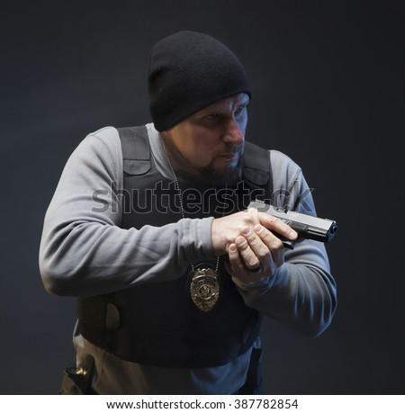Serious undercover special agent with a pistol about to engage. Studio photo shoot on dark background. - stock photo