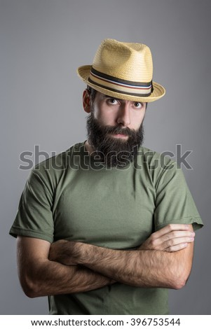 Serious unhappy bearded man with straw hat intense scowl at camera. Headshot portrait over gray studio background with vignette.