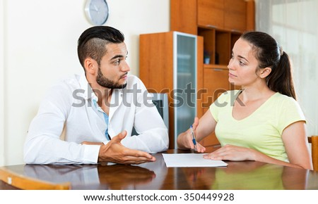 Serious  upset worried  male and female sitting with business papers