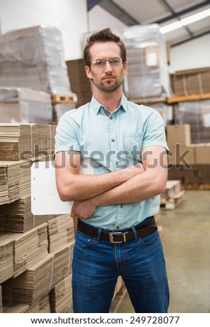 Serious warehouse manager standing with arms crossed in a large warehouse