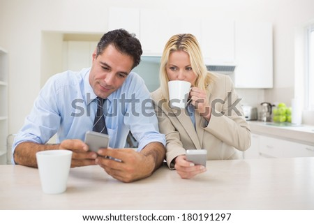 Serious well dressed couple with coffee cups text messaging in the kitchen at home