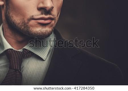Serious well-dressed hispanic man posing on dark background.  - stock photo