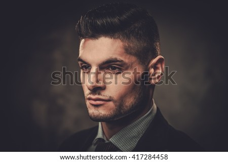 Serious well-dressed hispanic man posing on dark background.