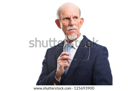Serious well dressed senior man holding glasses. Isolated.
