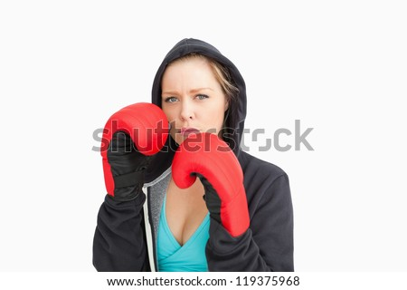 Serious woman boxing against white background