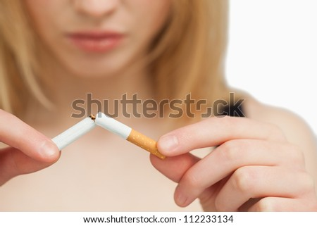 Serious woman breaking a cigarette against white background - stock photo