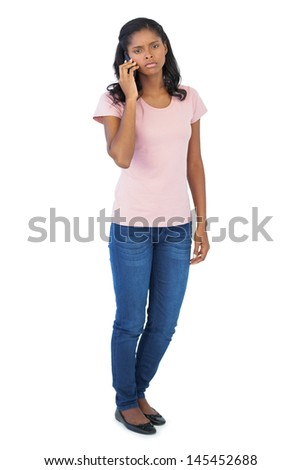 Serious woman calling with her mobile phone on white background - stock photo