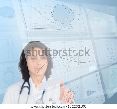 Serious woman doctor using futuristic interfaces - stock photo