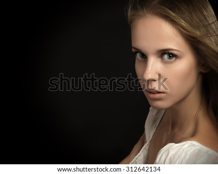 serious woman on black background looking in camera - stock photo