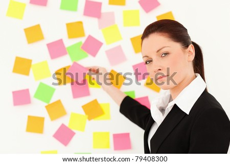 Serious woman putting re-positionable notes on a white wall against a white background