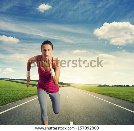 serious woman running on the road against blue sky and green field - stock photo