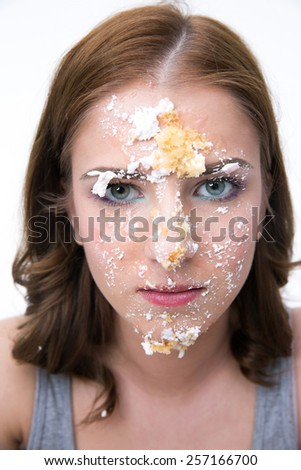 Serious woman sitting at the table with cake at her face - stock photo