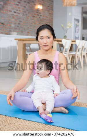 Serious woman sitting on mat with baby daughter at home