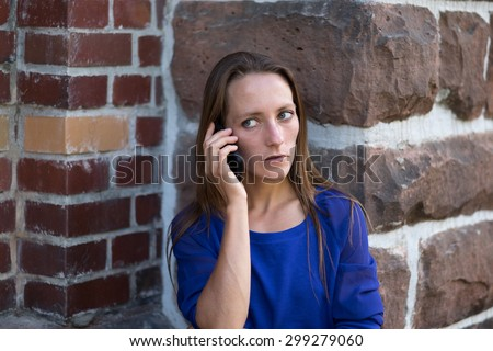 Serious woman standing at the corner of a building listening to a call on her mobile phone and staring thoughtfully to the side with a serious expression, head and shoulders - stock photo