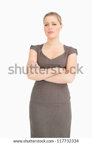 Serious woman standing with arms crossed against white background