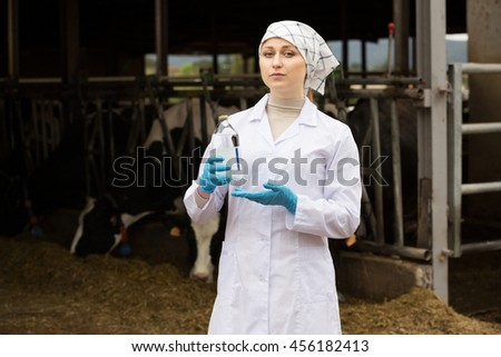 Serious woman veterinarian standing with test bottle next to cows on farm