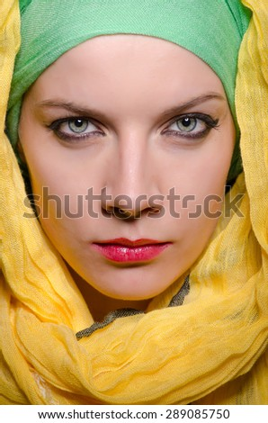 Serious woman wearing colourful headscarf - stock photo