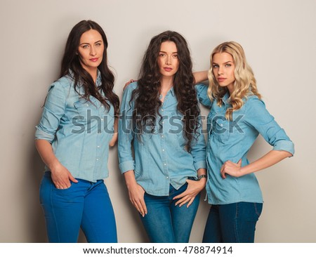 serious women leaning on their friend , standing against grey wall in studio
