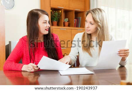 serious women looking financial documents at table in home or office